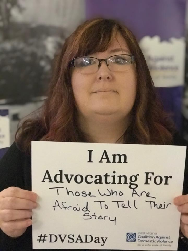 A person holding a sign that says I am advocating for those who are afraid to tell their story