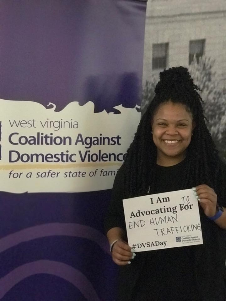 A person holding a sign that says I am advocating to end human trafficking