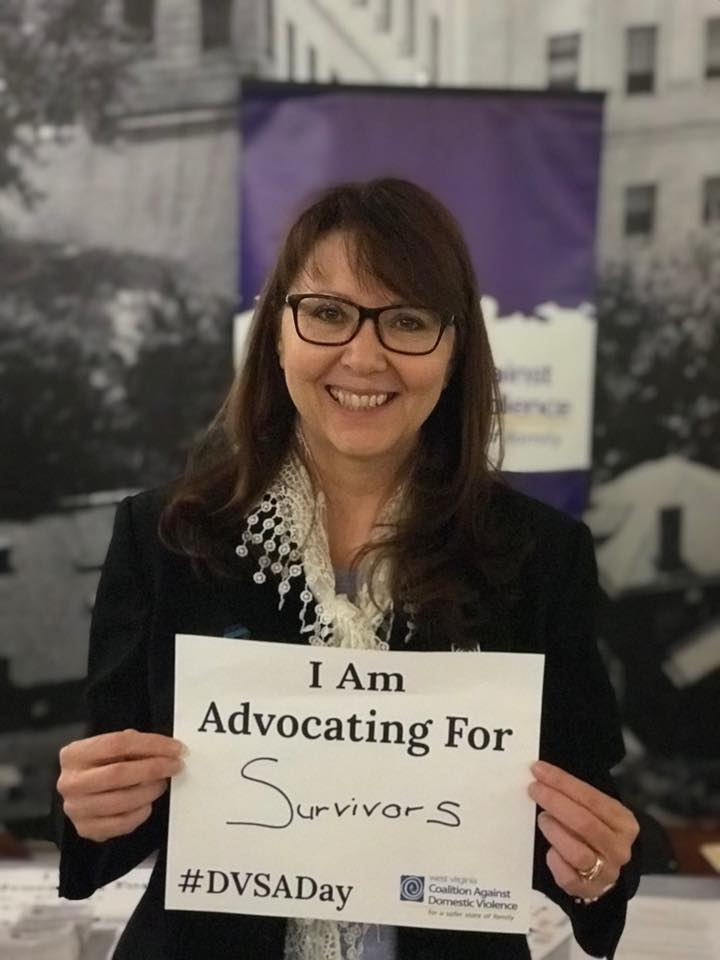 A person holding a sign that says I am advocating for survivors